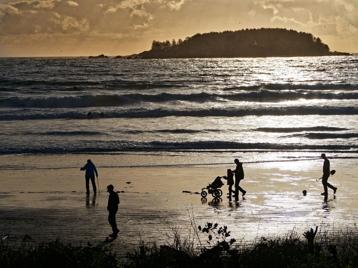 High angle view of silhouette people walking at beach during sunset