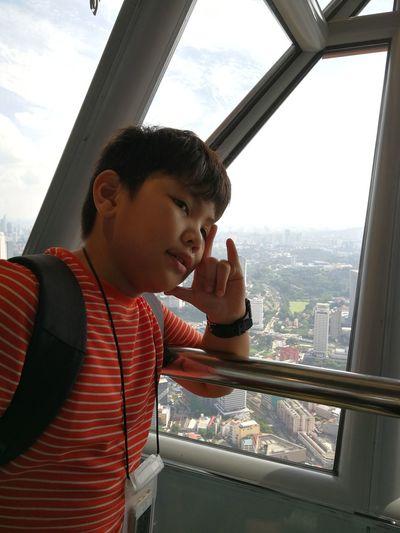 Boy looking standing by railing against window