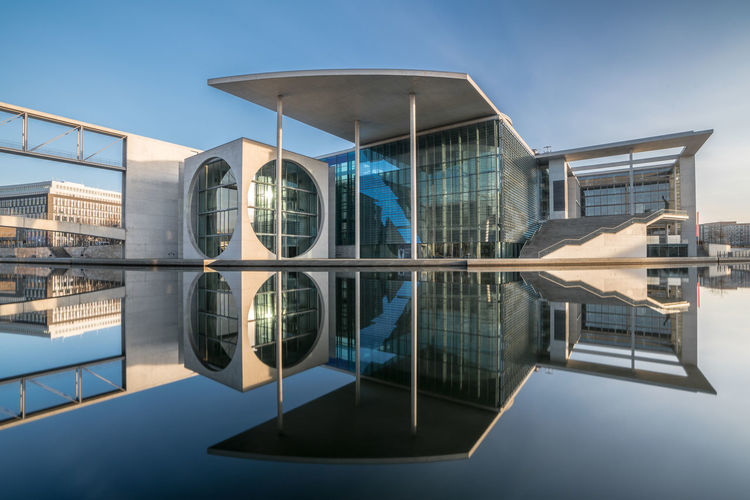 Modern building reflecting on water against clear blue sky during sunny day
