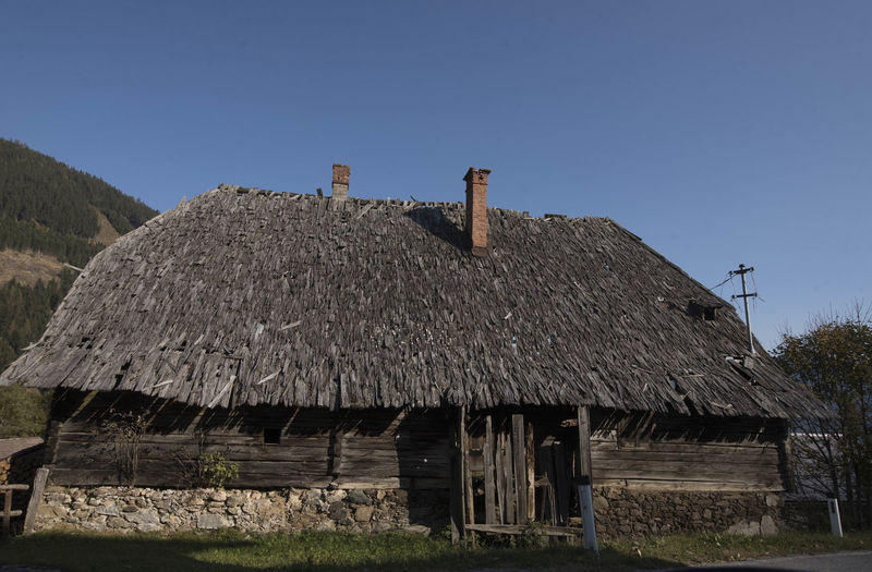 Old wooden house on landscape against clear sky