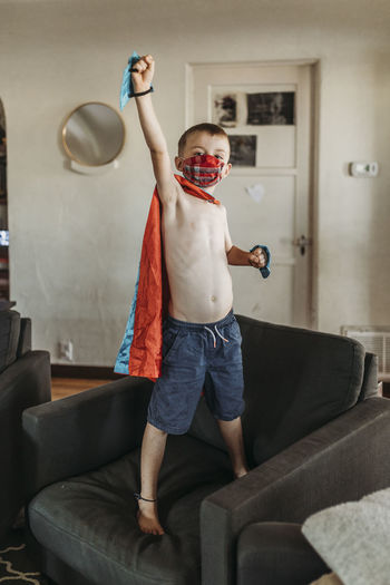 Full length of boy standing on sofa at home