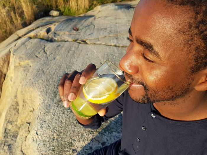 High angle view of young man having drink while sitting outdoors