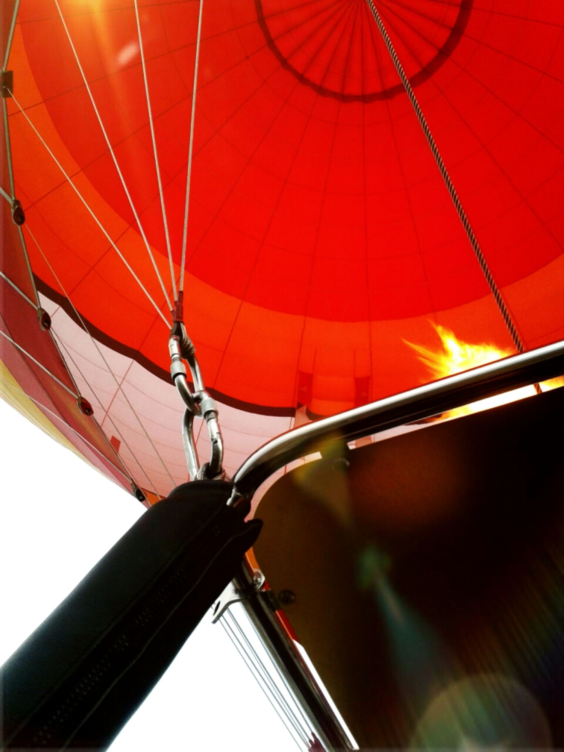 low angle view, transportation, part of, sky, red, mode of transport, cropped, motion, no people, close-up, travel, outdoors, sunset, lighting equipment, metal, orange color, day, mid-air, silhouette, built structure