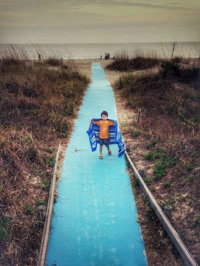 High Angle View Of Boy Standing On Walkway At Beach