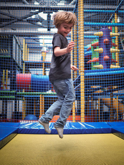 Full length of happy boy jumping over trampoline