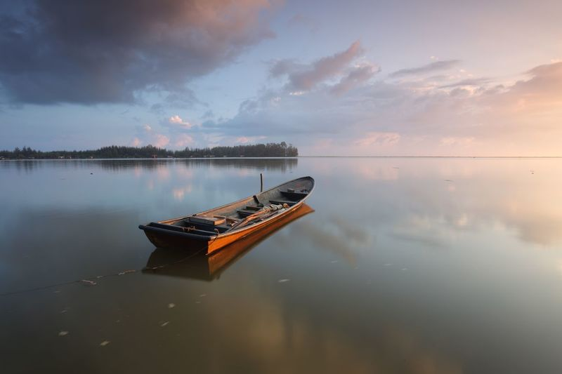 Fishing boat moored on lake during sunset