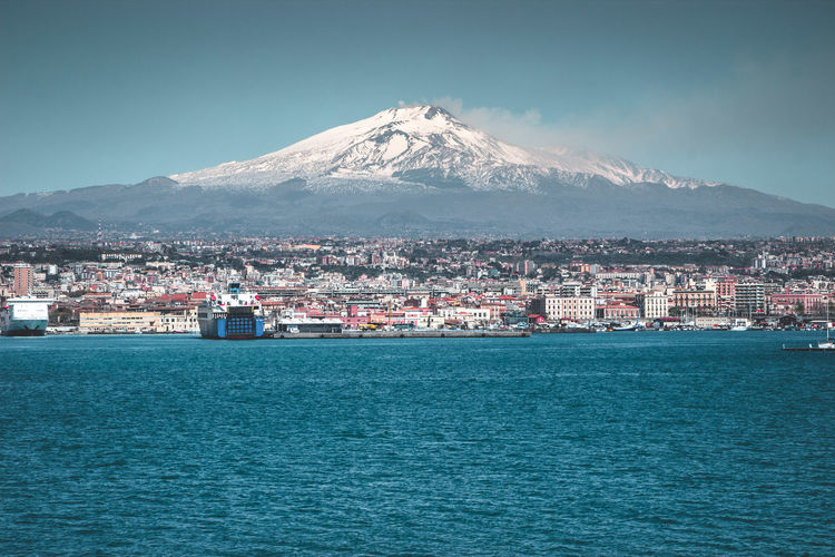 Volcano Etna and its city in a beautiful day Sicily Etna Mountain Architecture Sky Water Building Exterior Built Structure Sea Waterfront No People Scenics - Nature City Beauty In Nature Nature Snow Cold Temperature Snowcapped Mountain Building Volcano Winter Mountain Range Outdoors Cityscape Mountain Peak