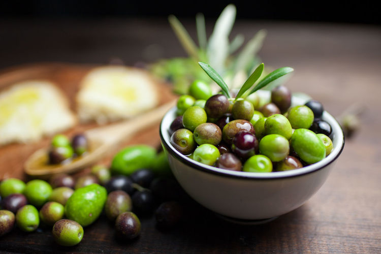 High angle view of green olives with bread on table