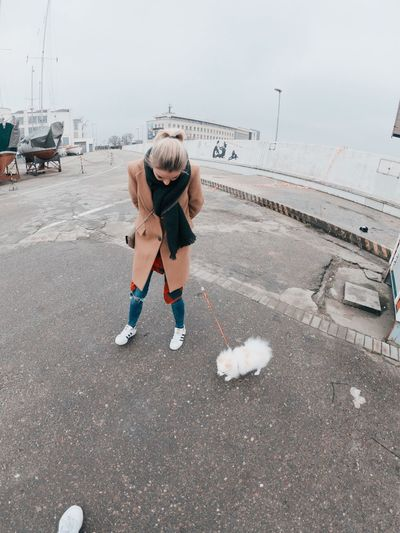 Woman with puppy standing on road