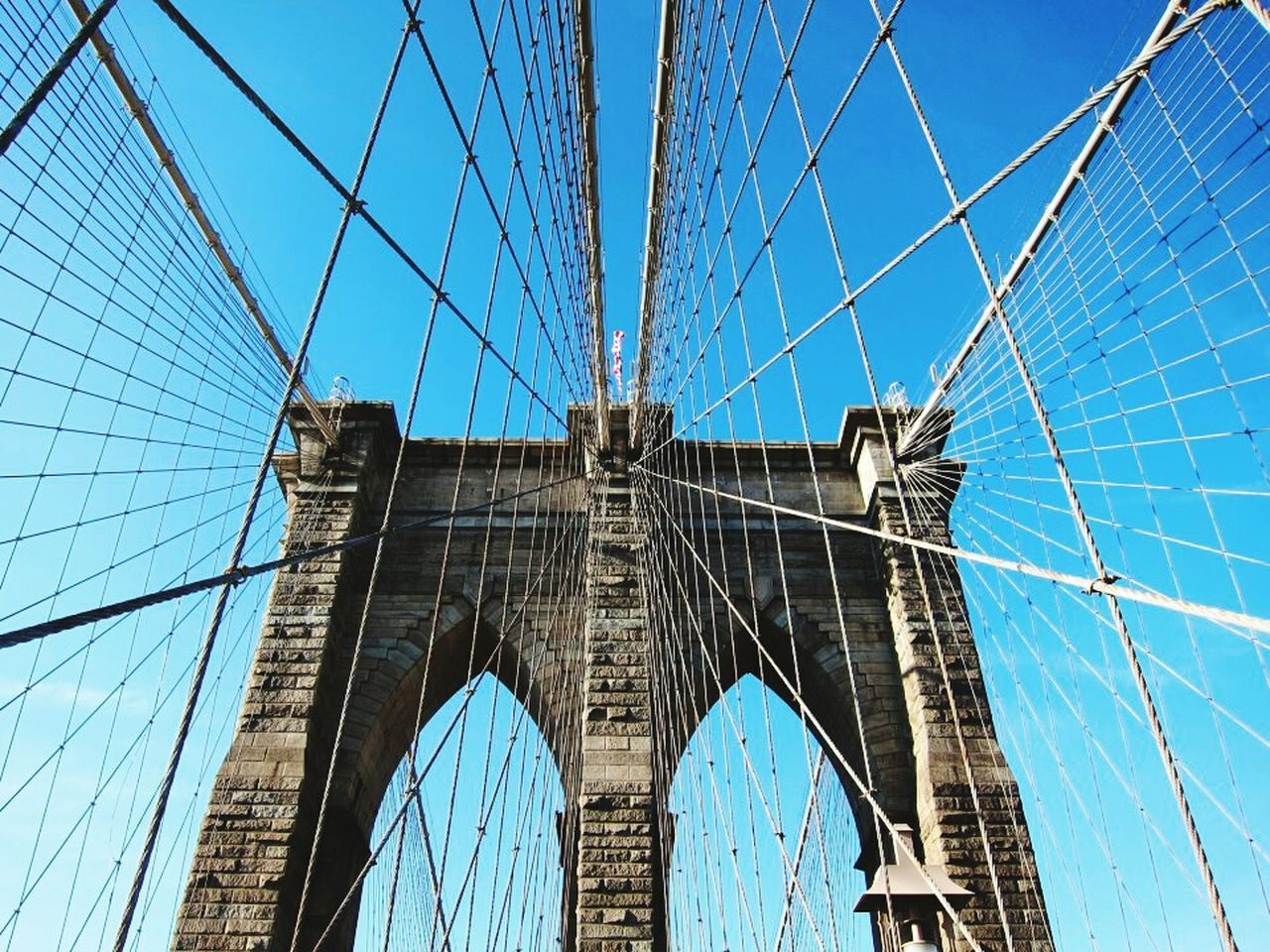 bridge - man made structure, architecture, built structure, connection, engineering, suspension bridge, low angle view, blue, transportation, sky, city, skyscraper, modern, travel destinations, outdoors, day, travel, building exterior, cable, no people, clear sky, urban skyline