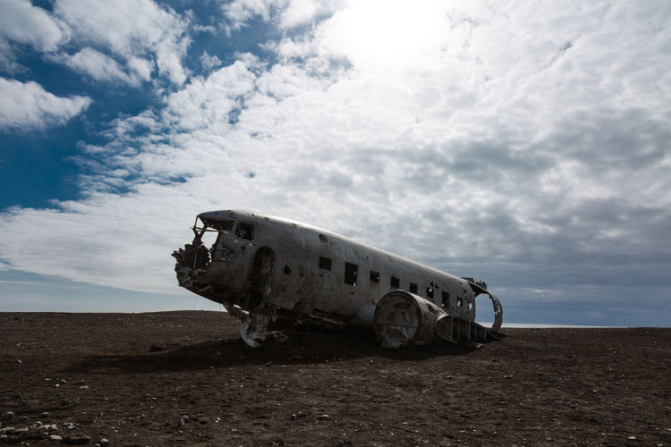 Abandoned airplane of land against sky