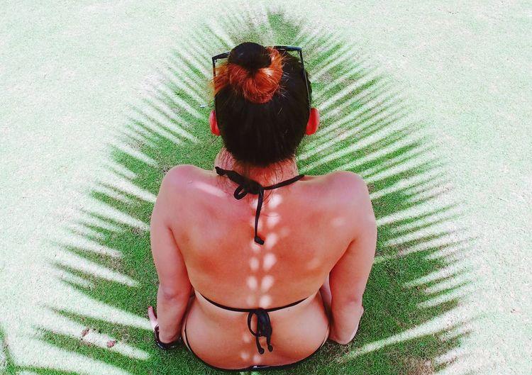 Shadow Of Leaf Falling On Woman Sitting At Beach