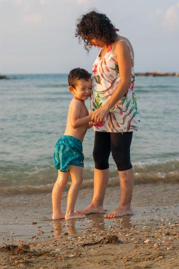 Full length of siblings at beach against sky