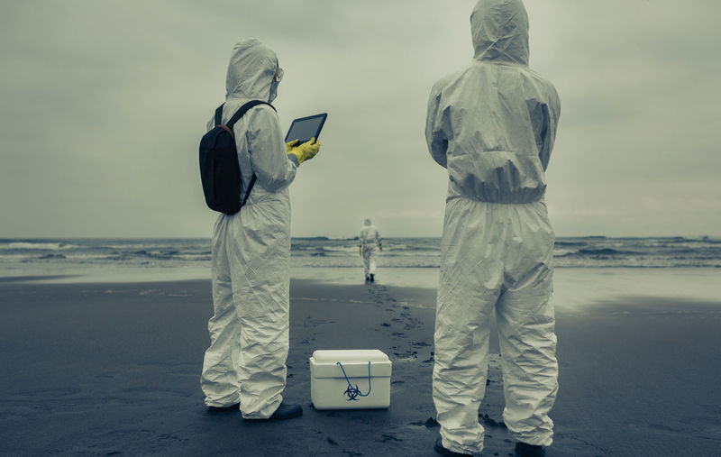 Rear view of man and woman with first aid kit standing on beach