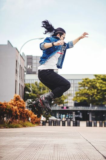 Young woman jumping in mid-air against sky in city
