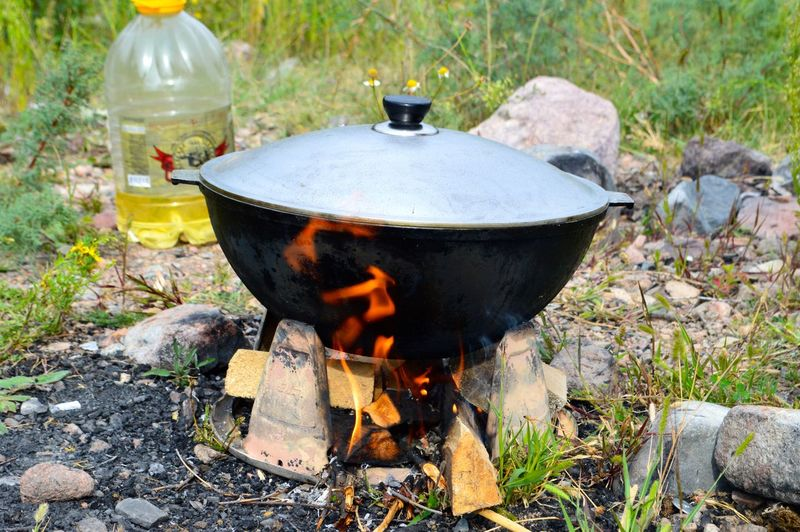 Low angle view of campfire and saucepan