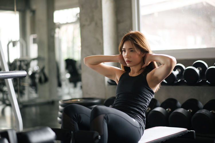Young Woman With Hands Behind Head Exercising In Gym