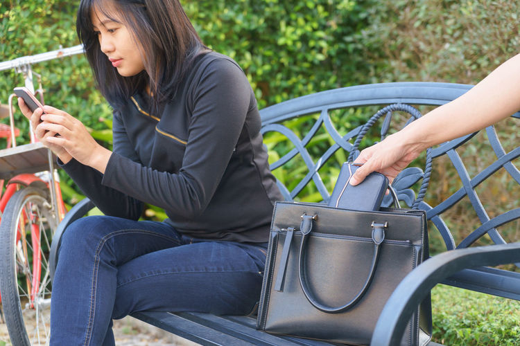 Cropped Hand Stealing Purse From Bag By Woman Using Phone On Bench