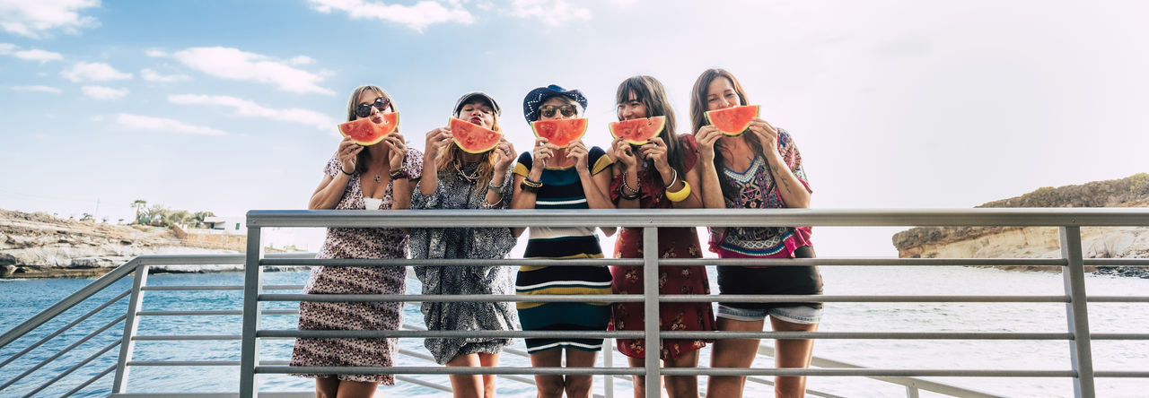 Portrait of friends eating watermelon while standing against sky