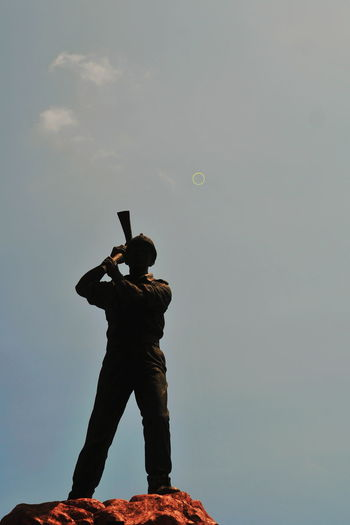 Low angle view of man using smart phone against sky