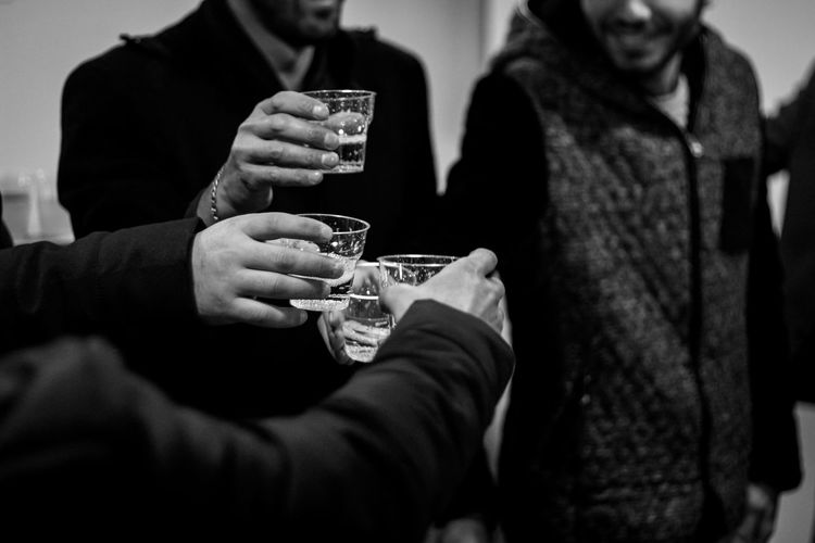 Friends Toasting Drinks While Standing In Room