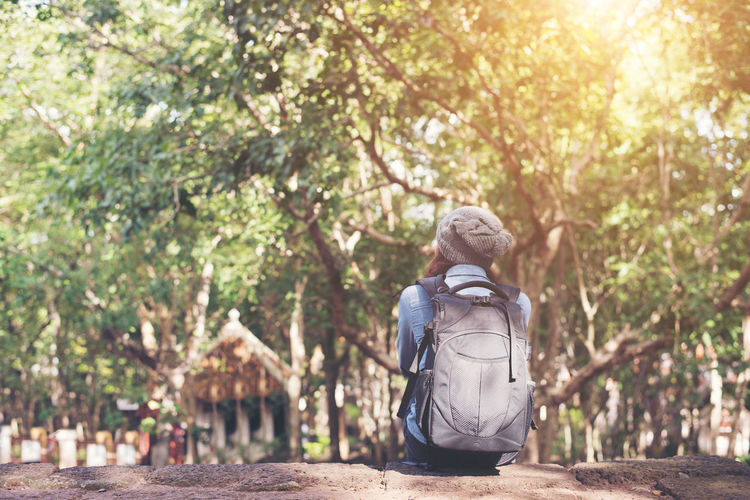 Rear View Of Female Tourist Sitting In Forest