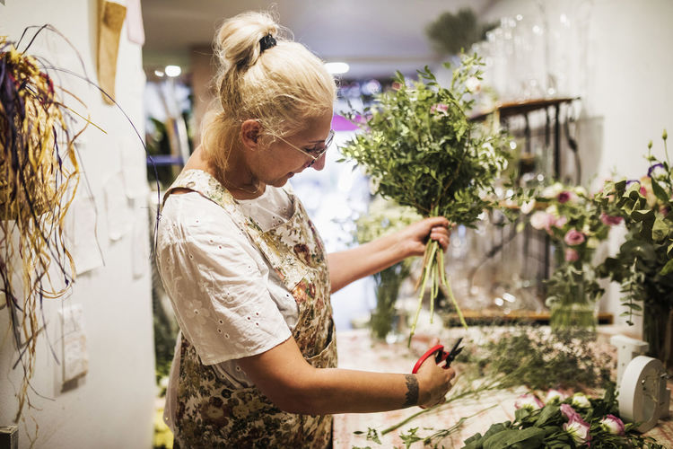 Woman standing by flowering plants at store
