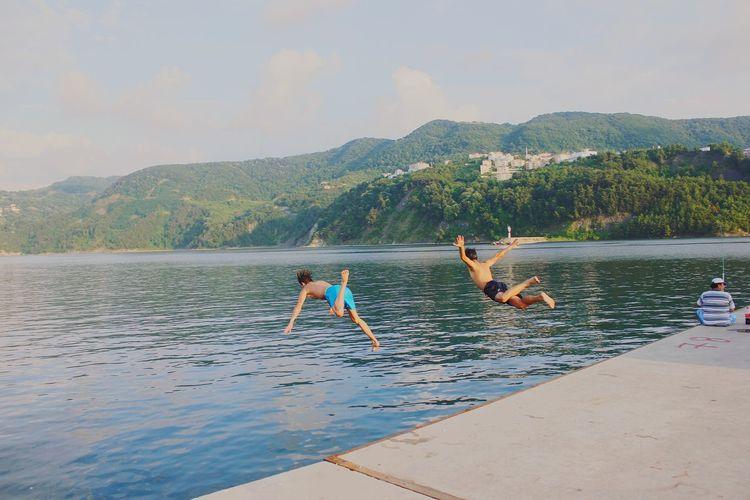 Men jumping on lake against sky