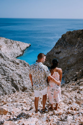 Rear view of couple looking at sea against sky
