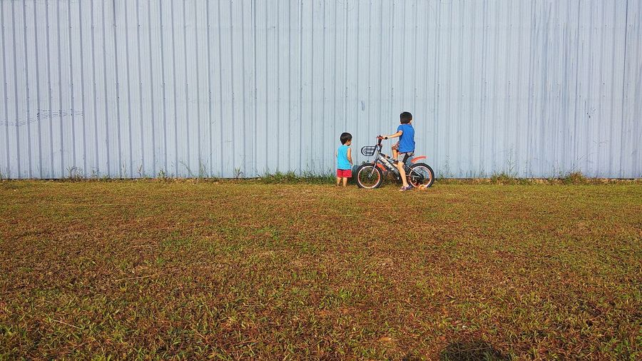 Brothers with bicycle on grassy field against wall