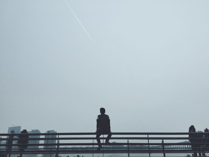 Rear view of man sitting on railing against sky