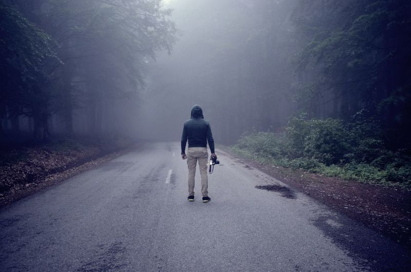 Rear view of man holding camera while standing on road amidst trees during foggy weather