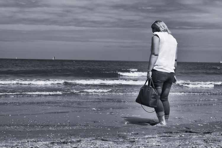 Rear View Of Woman Standing With Purse On Shore At Beach Against Sky
