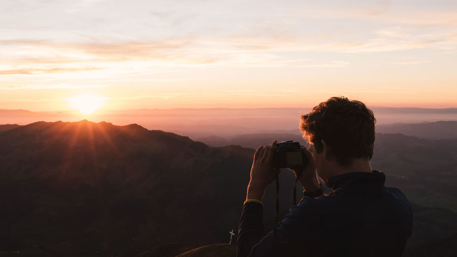 Man taking photos in the sunset light on a mountain Switzerlad Adventure Alps Beauty In Nature Camera - Photographic Equipment Digital Camera Lifestyles Mountain Mountain Range Nature One Person Orange Color Photographer Photographing Photography Themes Real People Sky Sun Sunlight Sunset