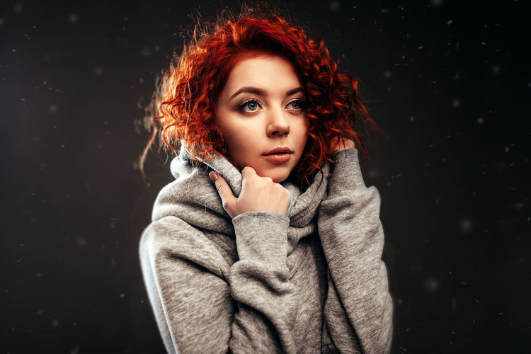 Redhead Woman Standing Against Wall