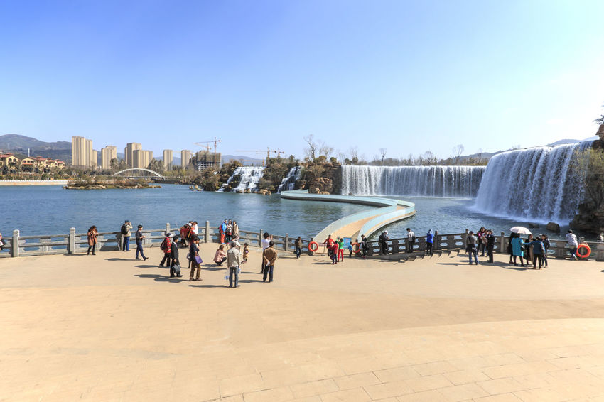 Kunming, China - March 4, 2016: Kunming Waterfall park featuring a 400 meter wide manmade waterfall. Kunming is Yunnan's capital Blue China City Clear Sky Dali Yunnan Dianchi Lake Indochina Kunming Kunming, China Large Group Of People Leisure Activity Lifestyles Lijiang Mixed Age Range Niulan River People Shore Southeastasia Tourist Tourists Vacations Water Waterfall Park Xinhua Yunnan