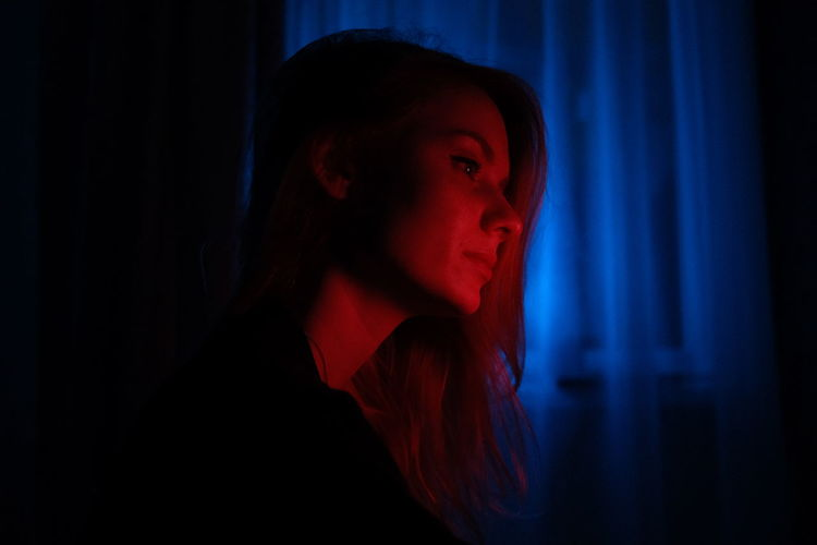 Portrait of beautiful young woman. girl in red and blue light at night