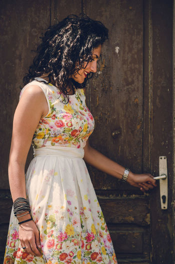 Side View Of Young Woman In Dress Opening Door