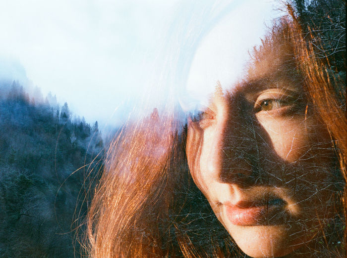 Double exposure of thoughtful woman and forest against clear sky