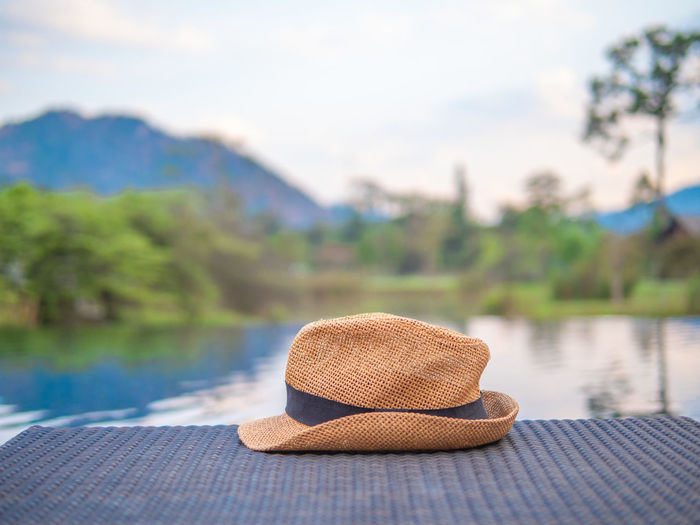 Close-up of hat on rock by lake against sky