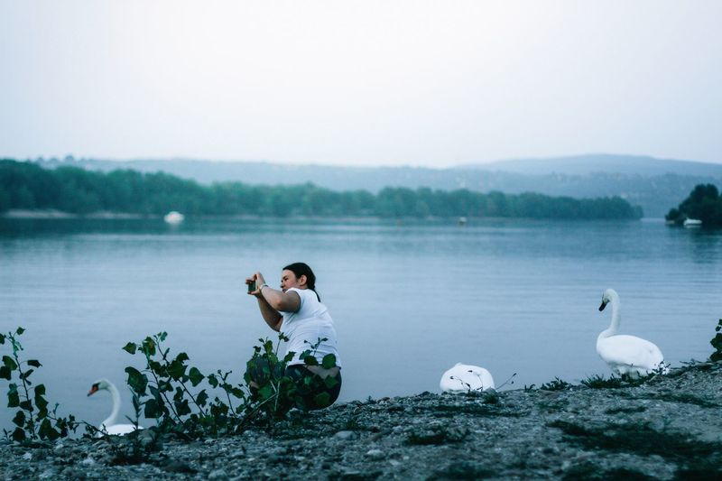 Side view of woman photographing while crouching at lakeshore