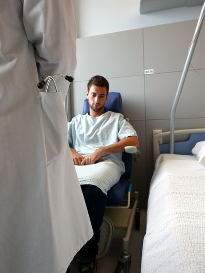 Close-Up Of Patient And Doctor In Hospital