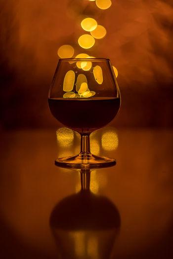 Close-up of illuminated wine glass on table