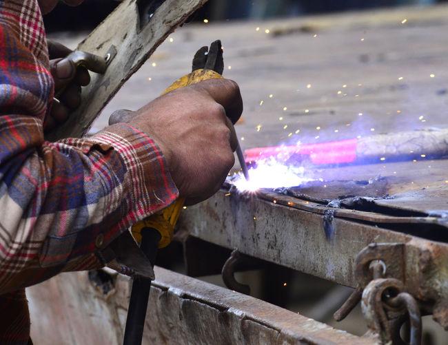 Cropped hands of male welder welding metal in factory