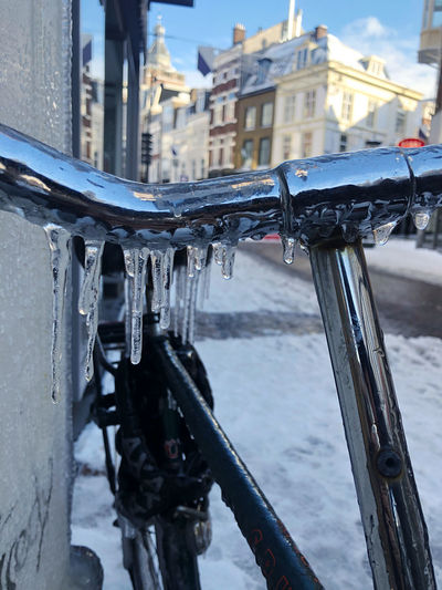 Close-up of metal railing in city during winter