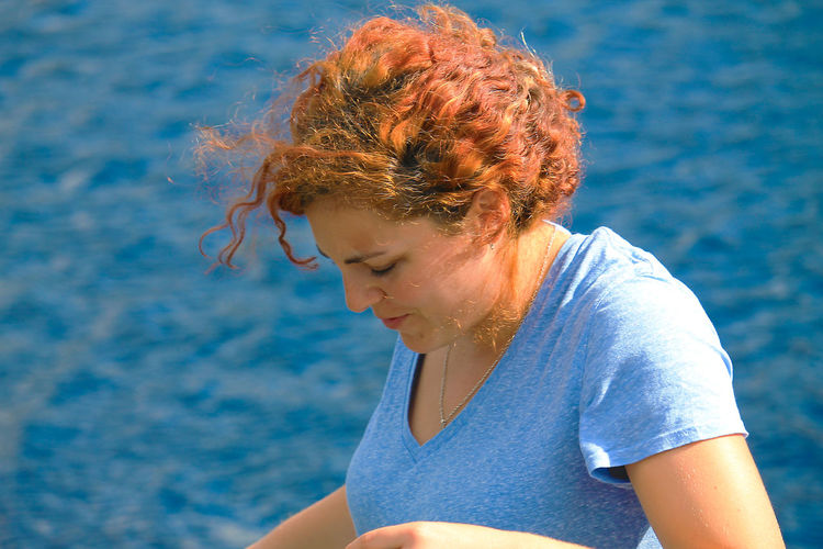 Woman looking down against sea at beach