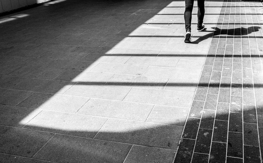 Low section of man walking on stone flooring