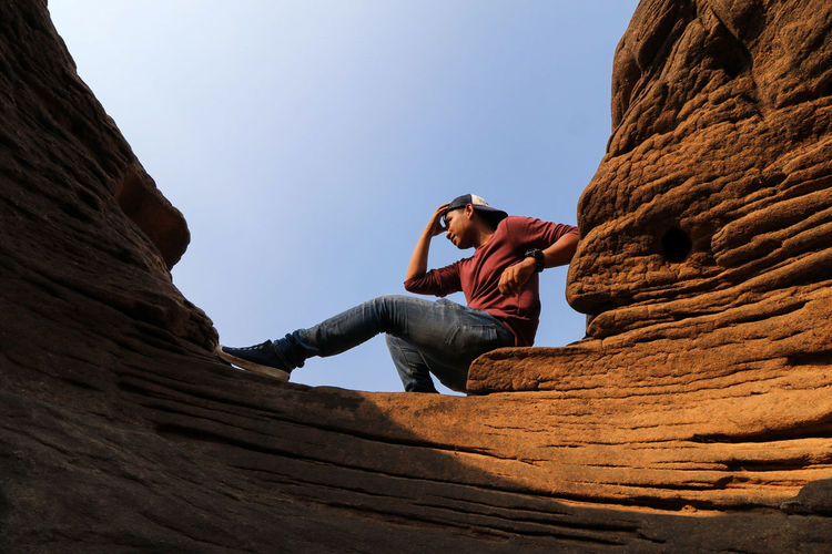 young man climbing on the rock Adventure Beauty In Nature Clear Sky Cliff Climbing Day Low Angle View Mountain Nature One Person Outdoors People Physical Geography Real People Rock - Object Rock Climbing Rock Formation Sky Young Adult