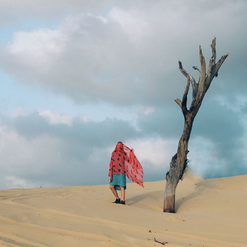 Woman Standing By Dead Tree At Desert Against Cloudy Sky