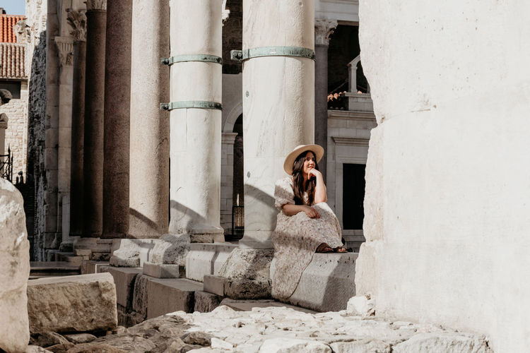 Full length of woman sitting against building